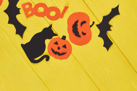 Holiday decorations for Halloween. Cat, bat, pumpkin and word boo cut out of paper on yellow background. Crafts for celebrating Halloween.