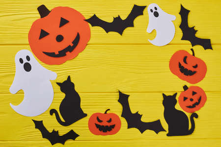 Yellow Halloween background with paper decorations. Halloween paper silhouettes with blank copy space. Halloween holiday theme.