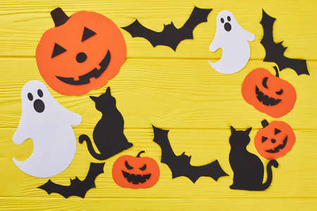 Halloween holiday composition. Yellow Halloween background with pumpkin cutouts, paper bats, ghosts and cats. Halloween holiday creativity.