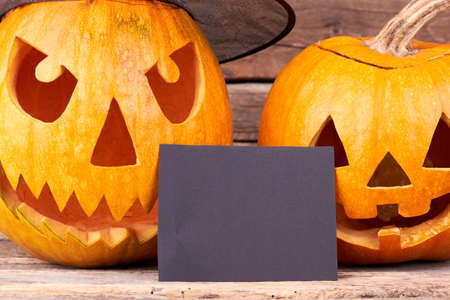 Halloween pumpkins and blank paper card. Close up carved pumpkins for Halloween holiday with blank card for greeting. Banco de Imagens