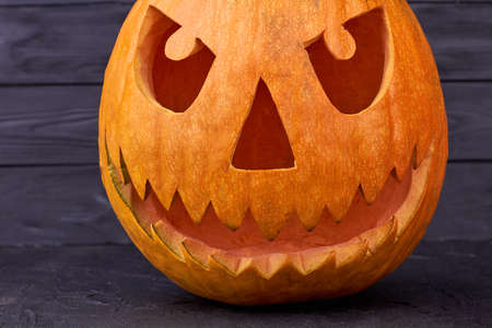 Scary Jack O Lantern face on dark wooden background. Pumpkin carving ideas for Halloween. Stock Photo - 130099412