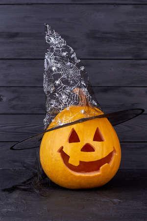 Halloween pumpkin dressed in magical witch hat. Funny Halloween pumpkin on dark background. Halloween holiday theme.