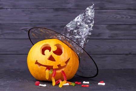 Halloween holiday theme. Funny Halloween pumpkin with magic hat and gummy worms on dark background. Creative ideas for Halloween party. Banco de Imagens