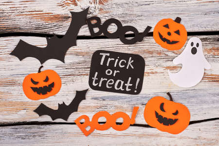 Halloween decoration trick or treat. Colorful paper cutouts for Halloween holiday on wooden background. Halloween diy paper crafts.