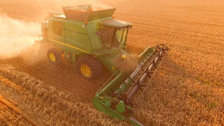 Combine on golden field. Agribusiness and technologies.