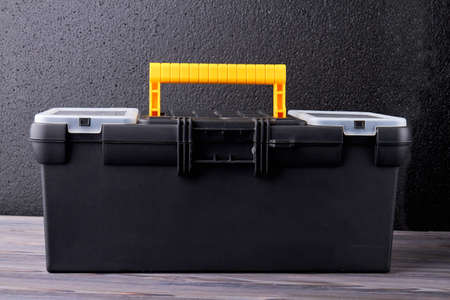 Black tool box with yellow handle. Case with tools, horizontal image. Concept of repair. Reklamní fotografie