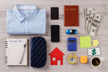 Busy person pattern on wooden table. Shirt, different personal and office stuff. Usual things around person.