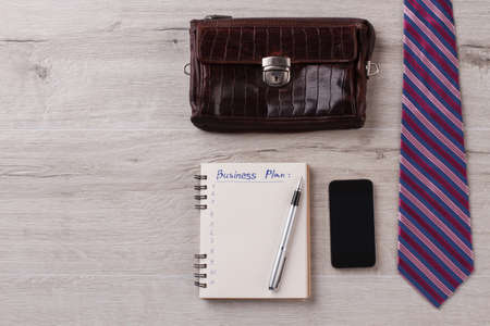 Businessman flatlay on wooden surface. Tie, notepad with pen. Mobile phone and leather wallet. Business concept. Фото со стока