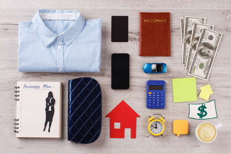 Shirt, various personal and office stuff. Busy person pattern on wooden table. Usual things around person.
