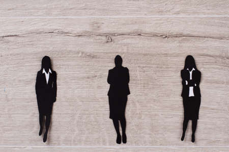 Black paper figures of business ladies. Three women in suits on wooden background. Business relations concept. Stock Photo