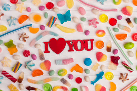 Tasty mixed colorful sweets for Valentines Day. Valentines holiday background with multicolored candies and inscription I love you. Stok Fotoğraf