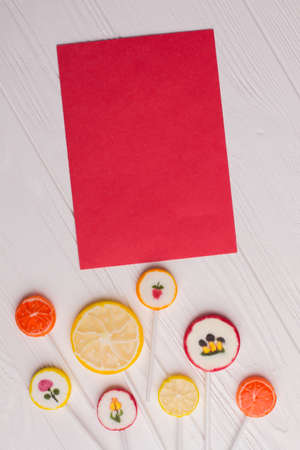 Candies and blank card, top view. Lemon and orange lollipops with red paper sheet on white wooden background.