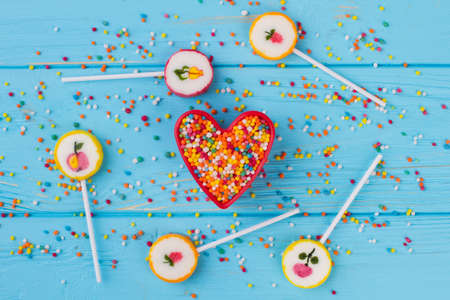 Assortment of colorful candies and lollipops. Heart-shaped cookie cutter with sprinkle candies and various lollipops on color background. Stock fotó