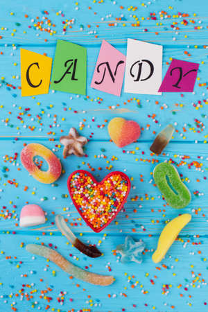 Inscription CANDY of colorful paper letters. Flat lay various candies and sweets on color wooden background.