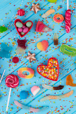 Different sweet candies on blue wooden table. Various multicolored candies on color wooden background, top view. Junk food concept. Stock fotó