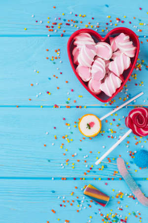 Birthday party background with multicolored candies. Heart-shaped box with marshmallows and various candies on wooden background. Top view with copy space. Stock fotó