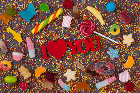 I love you inscription and candies. Background of the different multicolored candies. Valentine holiday concept. Stok Fotoğraf
