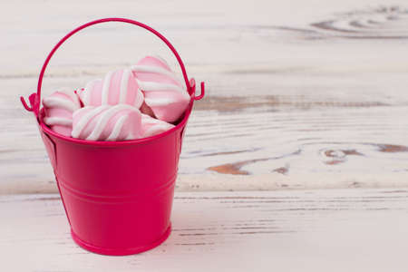 Small red bucket with marshmallows. Miniture metal bucket filled with marshmallow sweets, copy space. Minimal concept. Imagens