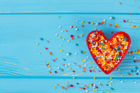 Valentines Day composition on blue background. Heart-shaped cookie cutter with candy sprinkles, copy space.