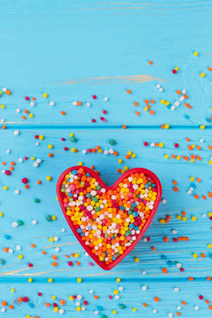 Heart-shaped cookie cutter filled with colorful sprinkles. Valentines holiday background with colorful candies, top view.