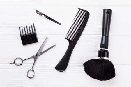 Set of hairdresser tools on white background. Scissors, comb and brush on wooden background. Main barbers tools.