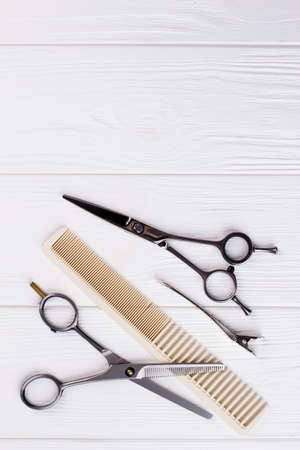Hairdressing scissors and comb, top view. Professional barbers tools on white background. Space for text.