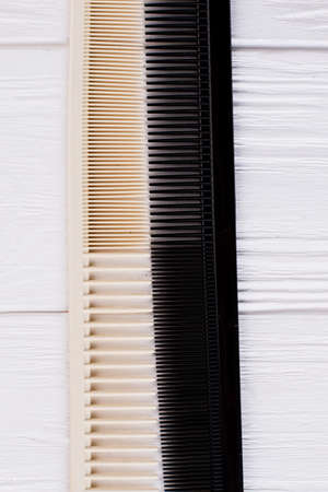 Two different plastic hair combs, top view. Hair combs on white wooden background. Personal hair accessory. Zdjęcie Seryjne