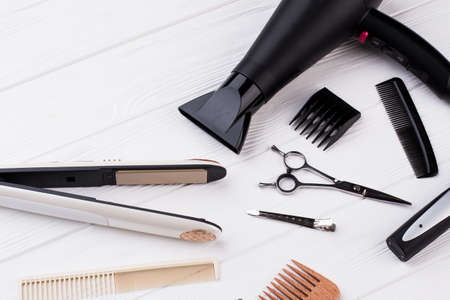Hairdresser tools and accessories on wooden table. Hair straightener, combs, scissors and hair dryer. Working equipment of professional hairdreseser.