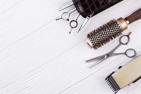 Hairdressing equipment on wooden background. Must-have hairdressing tools on white surface. Space for text.