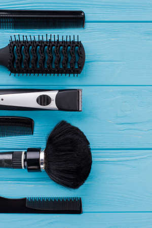 Hairdressing equipment on color background. Set of hairdresser tools on blue wood. Space for text.