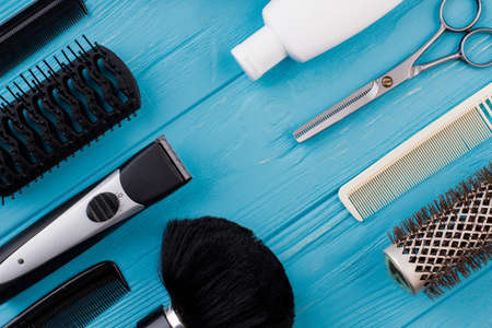 Professional hairdressing tools on blue wooden background. Barber shop equipment on color background. Flat lay composition.