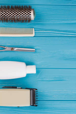 Hairdresser set on blue wooden background. Hair brushes, scissors, shampoo bottle and electric clipper. Space for text.