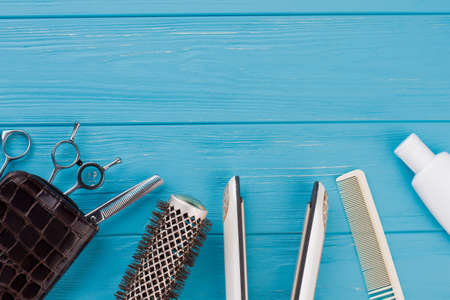 Hairdresser tools on blue wooden background. Hairdressing equipment on color background. Space for text.