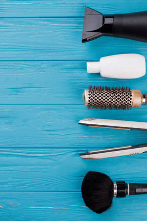Women hair care set. Hairdresser tools on blue wooden background. Space for text. Zdjęcie Seryjne