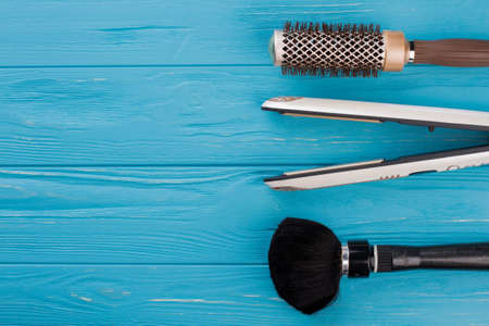 Hair care tools on wooden background. Hair brushes and hair straightener on color surface. Space for text. Zdjęcie Seryjne
