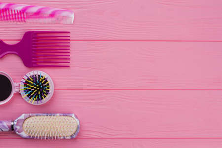 Colorful hair brushes on pink background. Colored hair brushes and combs. Space for text.