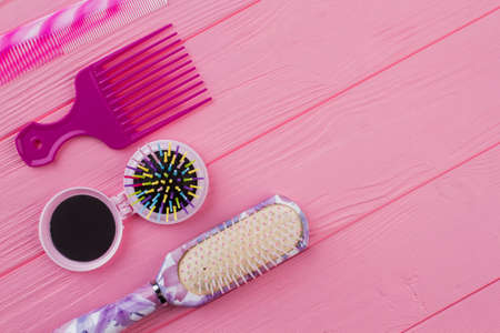 Various colored brushes and combs for hair. Hair brushes on pink wooden table. Space for text. Zdjęcie Seryjne