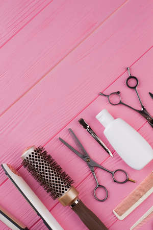 Hairdressing tools on pink background. Professional hairdresser equipment set. Space for text.