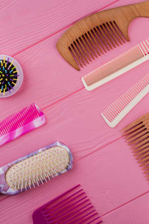 Hair combs and brushes on pink background. Various hair brushes on color wooden table. Flat lay, top view.