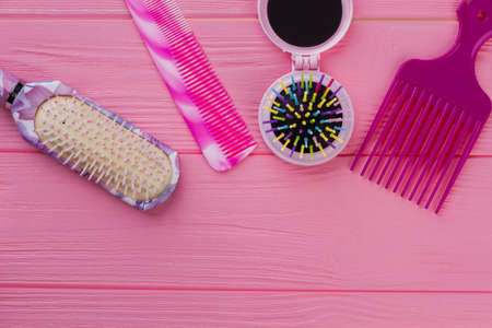 Female combs and brushes on color background. Colored brushes on pink wooden table. Zdjęcie Seryjne
