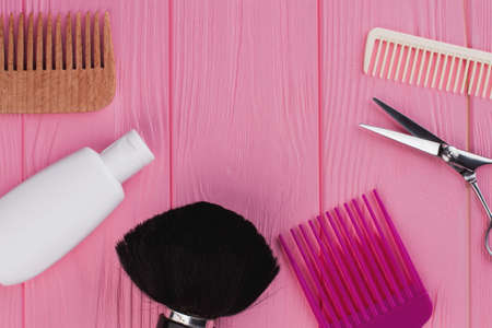 Various hairdresser tools on wooden table. Combs, scissors and shampoo on pink background. Equipment for hair care.