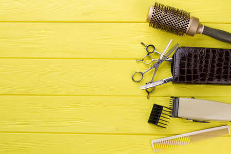 Hairdresser tools on yellow table. Objects for hairdresser on color background. Space for text.