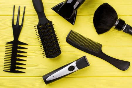 Set of hairdresser tools. Professional barber equipment on yellow wooden background.