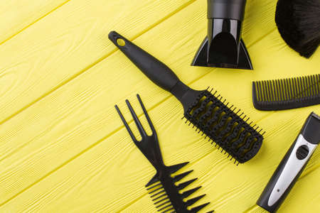 Hairdresser equipment on yellow wooden background. Tools for hairdresser.