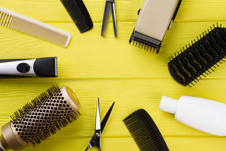 Hairdresser tools on yellow wooden background. Frame with hairdresser equipment. Space for text. Zdjęcie Seryjne