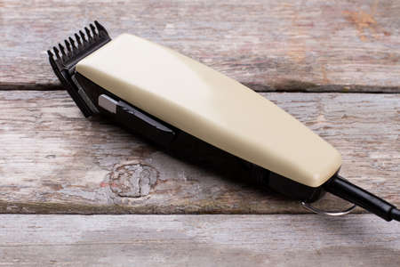 Electric hair clipper on wooden background. Machine for hairstyle on rustic wooden surface.