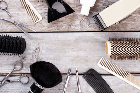 Hairdresser tool set. Combs, brushes and other hair accessories on rustic wooden background. Space for text. Zdjęcie Seryjne