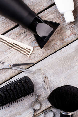Hairdresser tools on vintage wooden background. Hairdresser equipment on rustic wooden table. Flat lay, top view.