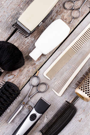 Hairdresser set for men on wooden background. Various hairdresser tools on rustic wood table. Flat lay, top view.