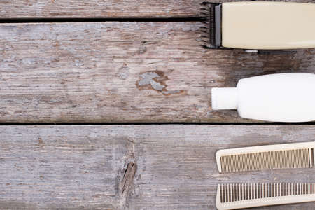Combs, electric clipper and shampoo. Male hair care products on wooden background. Space for text.